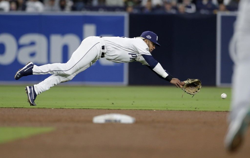 San Diego Padres shortstop Fernando Tatis Jr. can't reach a ground ball hit for a two-RBI single by the Seattle Mariners' Tim Beckham during the fifth...