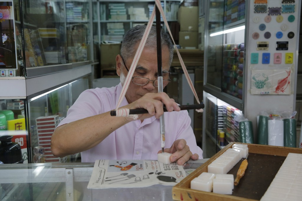 In this April 18, 2019, photo, Cheung Shun-king, 65-year-old mahjong game tiles maker, engraves a character on a tile in his shop in Kowloon's old nei...