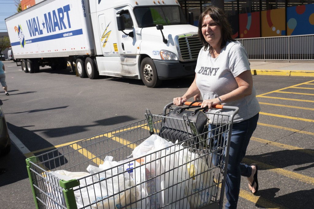 A customer pushes her cart into the parking lot after shopping at a Walmart Neighborhood Market, Wednesday, April 24, 2019, in Levittown, N.Y. The com