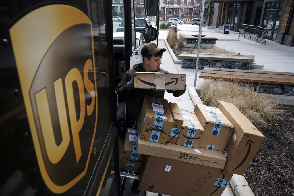 FILE- In this Dec. 19, 2018, file photo a UPS driver prepares to deliver packages. United Parcel Service Inc.  reports earns on Thursday, April 25, 20...