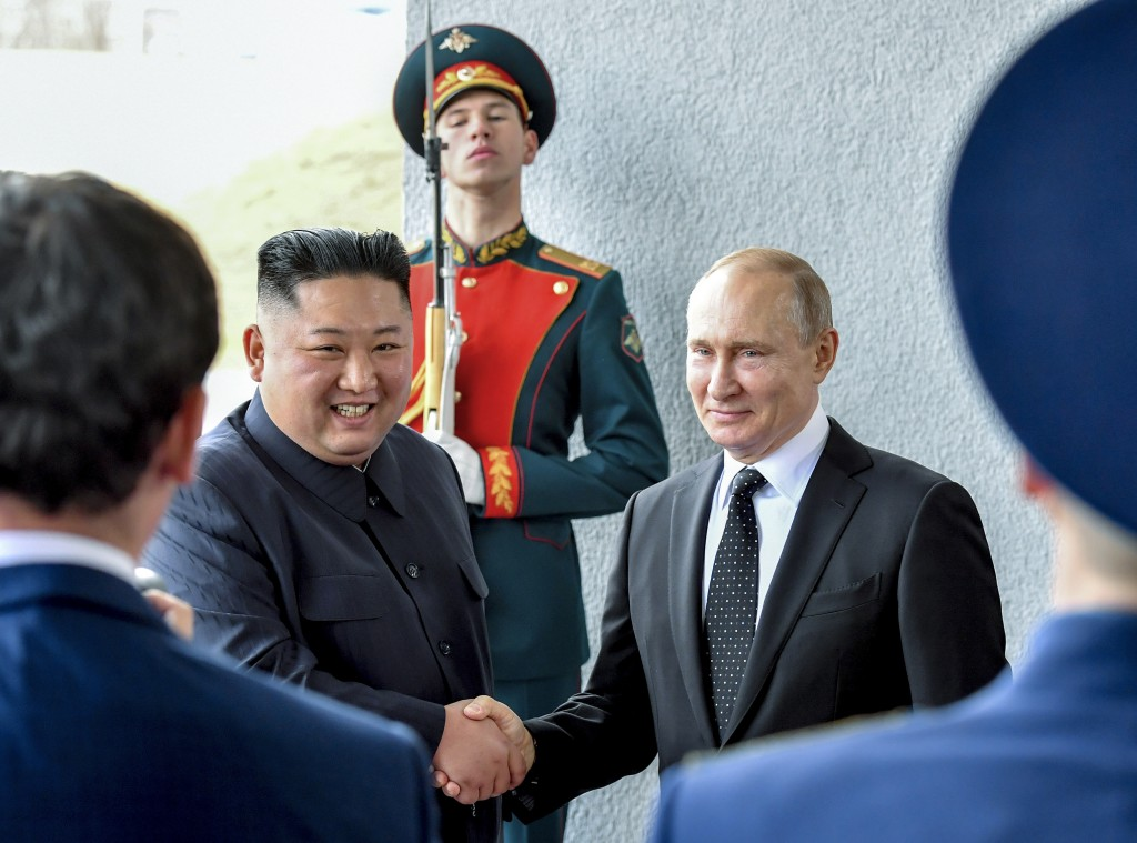 Russian President Vladimir Putin, center right, and North Korea's leader Kim Jong Un shake hands during their meeting in Vladivostok, Russia, Thursday...