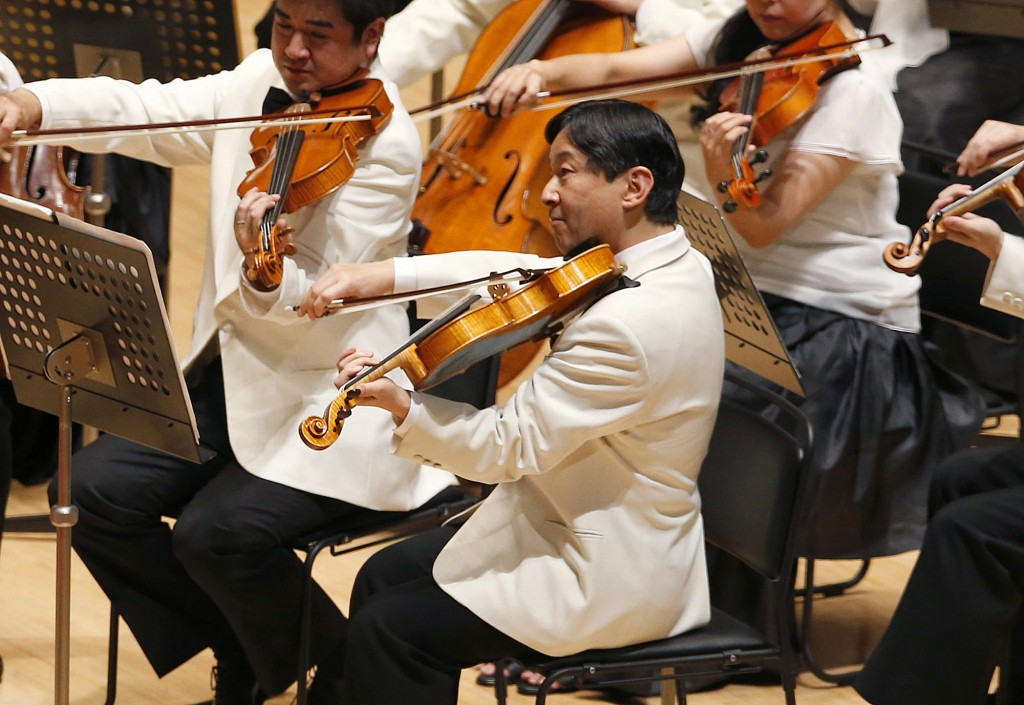FILE - In this July 7, 2013, file photo, Japan's Crown Prince Naruhito, center, plays the viola during a concert of the Gakushuin university's alumni ...