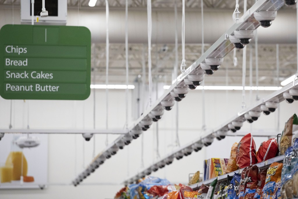 Dozens of cameras hang above an aisle at a Walmart Neighborhood Market, Wednesday, April 24, 2019, in Levittown, N.Y. This living lab, dubbed Walmart'