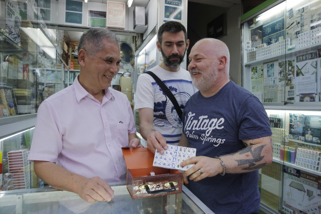 In this April 18, 2019, photo, Cheung Shun-king, a mahjong game tiles maker, left, chats with two customers from France at his store in Hong Kong. Han...