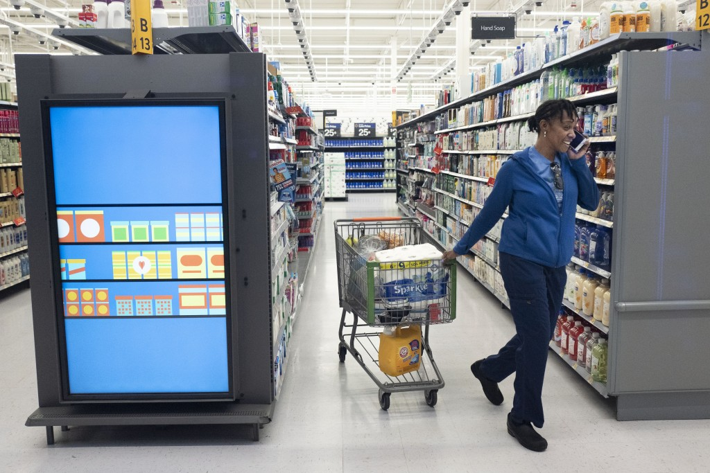 A customer pulls her shopping cart past an information kiosk at a Walmart Neighborhood Market, Wednesday, April 24, 2019, in Levittown, N.Y. Kiosks an