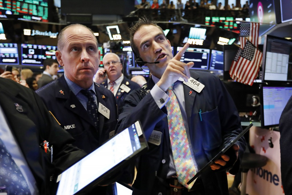 FILE - In this April 18, 2019, file photo traders Michael Urkonis, left, and Gregory Rowe, right, work on the floor of the New York Stock Exchange. Th...