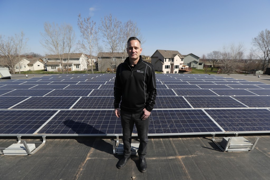 In this April 15, 2019, photo, Todd Miller stands next to solar panels on the roof of his solar installation business in Ankeny, Iowa. For years wind ...