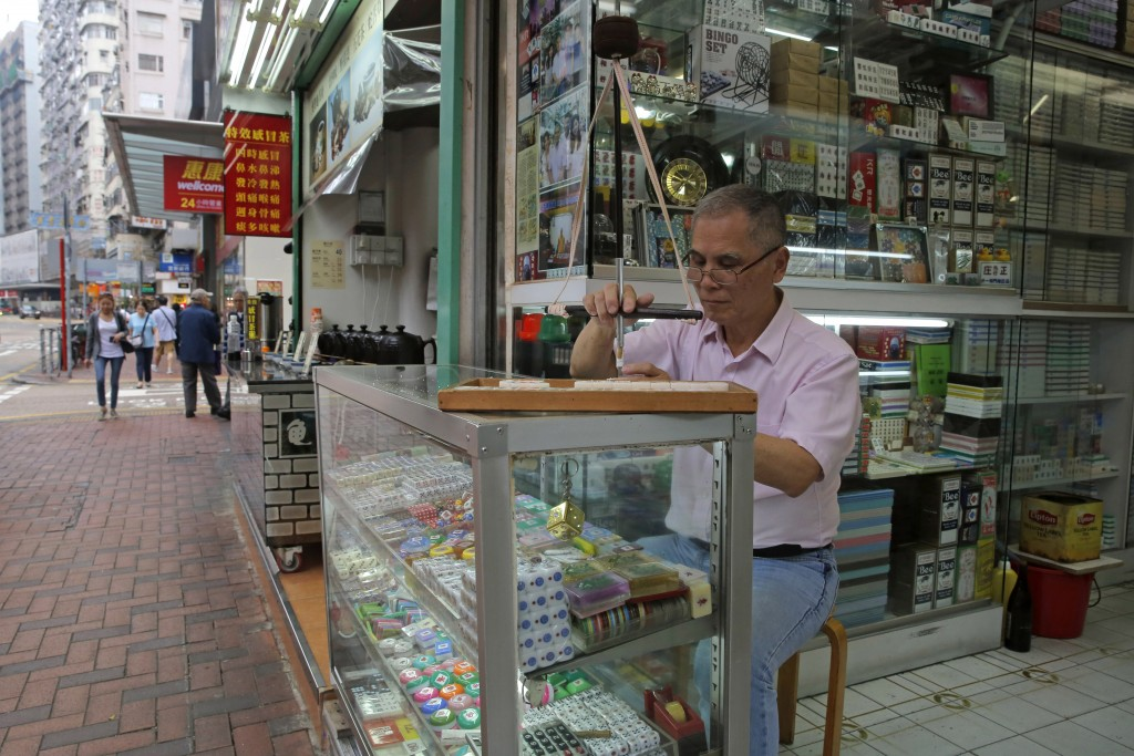In this April 18, 2019, photo, Cheung Shun-king, 65-year-old maker of the popular table-top game mahjong tiles, engraves a character on a tile in his ...