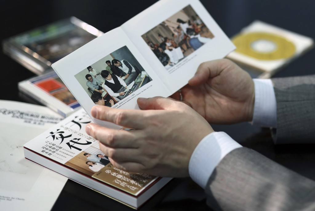 In this March 9, 2019, photo, Toshio Shiraishi, violoncello of amateur Shunyukai Symphony Orchestra shows a booklet of their CD including a picture of...