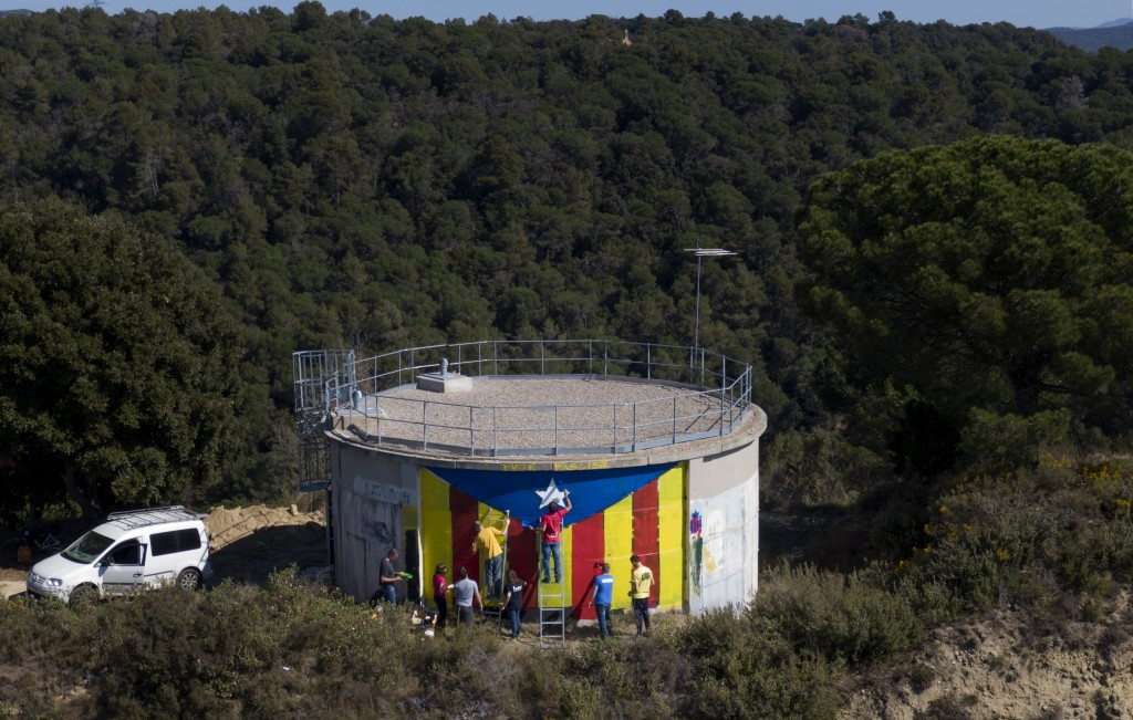 """In this Sunday, March 24, 2019 photo, activists paint an """"estelada"""" or independence flag on a water tank near Barcelona, Spain. A substantial pool of ..."""