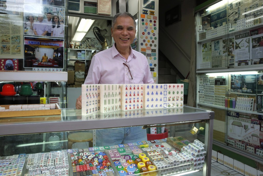In this April 18, 2019, photo, Cheung Shun-king, 65-year-old mahjong game tiles maker, poses with his mahjong tiles in his decades-old store 100 squar...