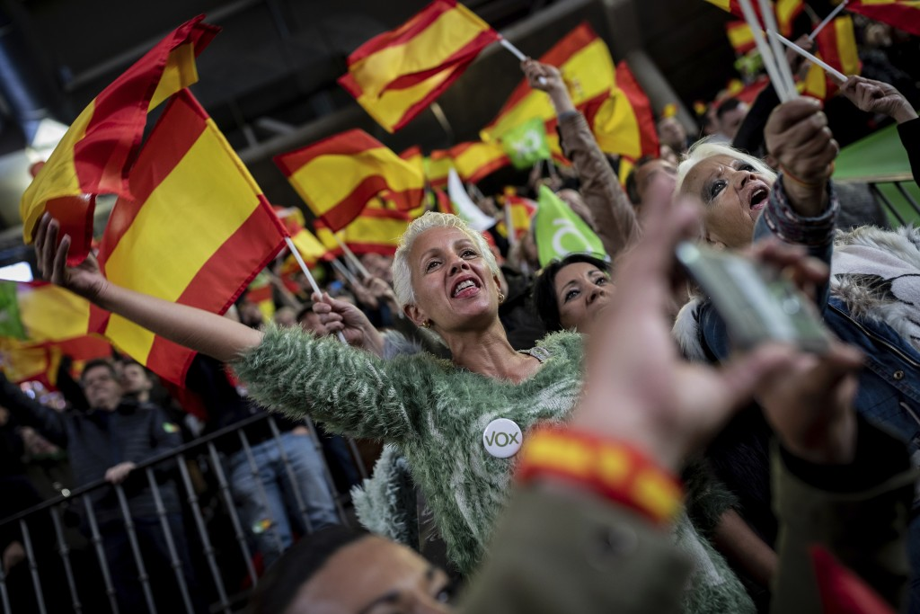 In this Saturday, April 6, 2019 photo, supporters of Spain's far-right Vox Party wave Spanish and VOX flags during a party event in Leganes, on the ou...