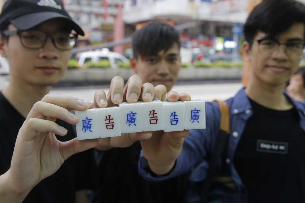 In this April 18, 2019, photo, three students hold their tailor-made mahjong game tiles with Chinese characters engraved by Cheung Shun-king at a shop...