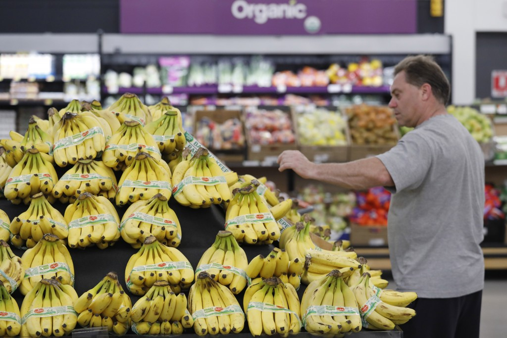 A customer shops for bananas at a Walmart Neighborhood Market, Wednesday, April 24, 2019, in Levittown, N.Y. High resolution cameras suspended from th