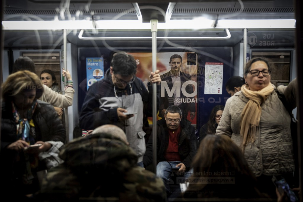 In this Wednesday, April 24, 2019 photo, a banner of Spanish election runner Citizens party's Albert Rivera is seen in the background in a subway stat...
