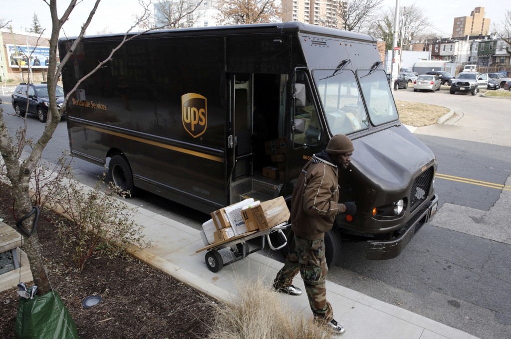 FILE - In this Dec. 19, 2018, file photo a UPS driver prepares to deliver packages in Baltimore. United Parcel Service Inc. reports earns on Thursday,...