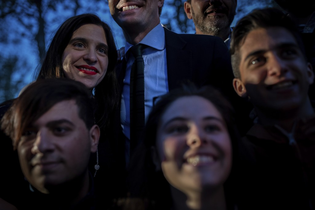 In this Tuesday, April 16, 2019 photo, Popular Party's candidate Pablo Casado, top and center, smiles while posing for snapshots with supporters after...