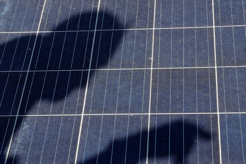 In this Monday, April 15, 2019, photo Todd Miller casts a shadow on a solar panel on the roof of his solar installation business in Ankeny, Iowa. When