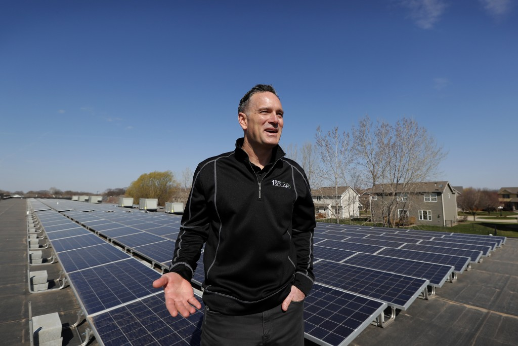 In this April 15, 2019, photo Todd Miller stands next to solar panels on the roof of his solar installation business in Ankeny, Iowa. When Miller bega...