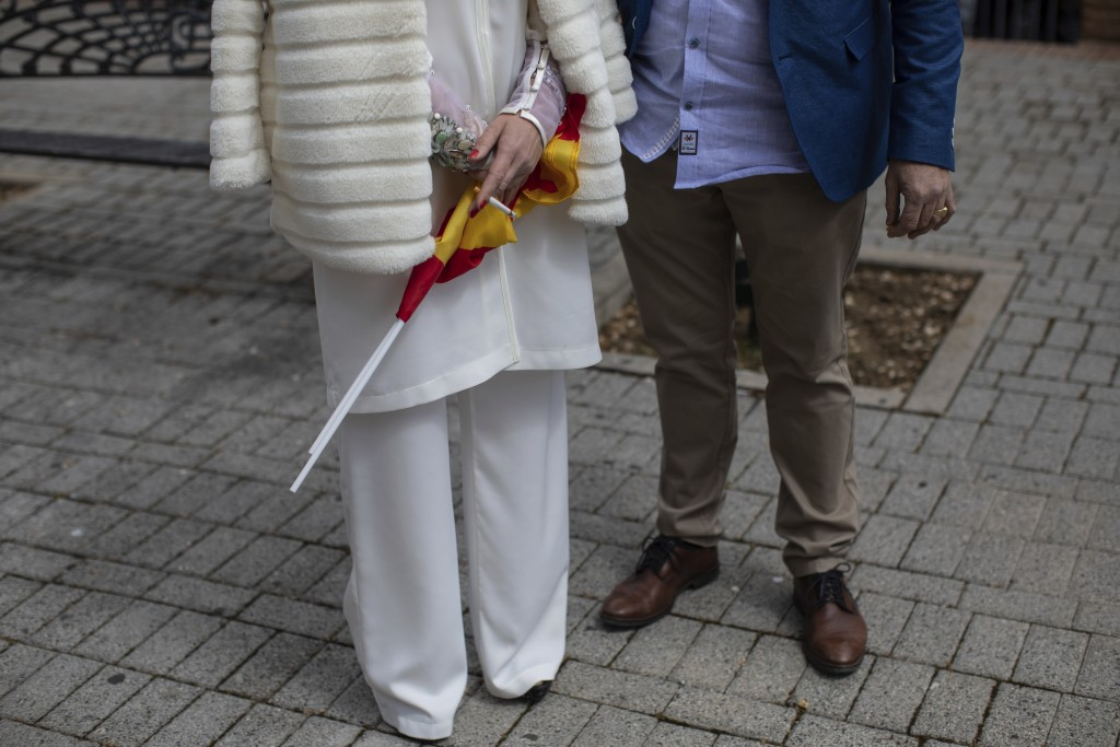 In this Saturday, April 6, 2019 photo, voters smoke a cigarette at the end of an event hosted by Spain's far-right Vox Party in Leganes, on the outski...
