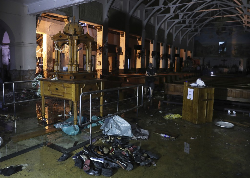 Shoes and other belongings of worshippers lie stacked up inside St. Anthony's Church in Colombo, Sri Lanka, Friday, April 26, 2019. Priests have allow