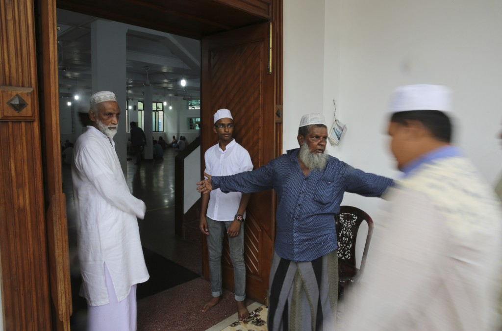 A Sri Lankan Muslim guides people for Friday prayers inside a mosque, in Colombo, Sri Lanka, Friday, April 26, 2019. Across Colombo, there was a visib