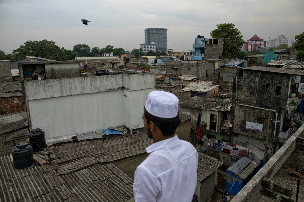 A Muslim volunteer stands in a roof of a mosque to spot possible attackers during Friday prayers in Colombo, Sri Lanka, Friday, April 26, 2019. Religi