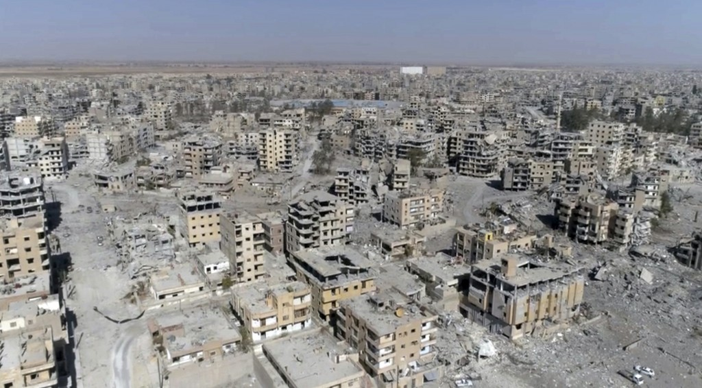FILE - This Oct. 19, 2017 file photo, a frame grab made from drone video shows damaged buildings in Raqqa, Syria. Amnesty International and Airwars, a