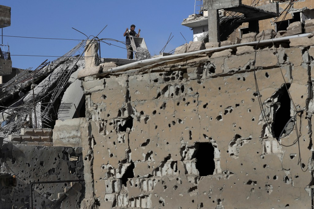 In this April 5, 2018 photo, a man removes rubble from his house that was damaged during fighting between U.S.-backed Syrian Democratic Forces fighter...