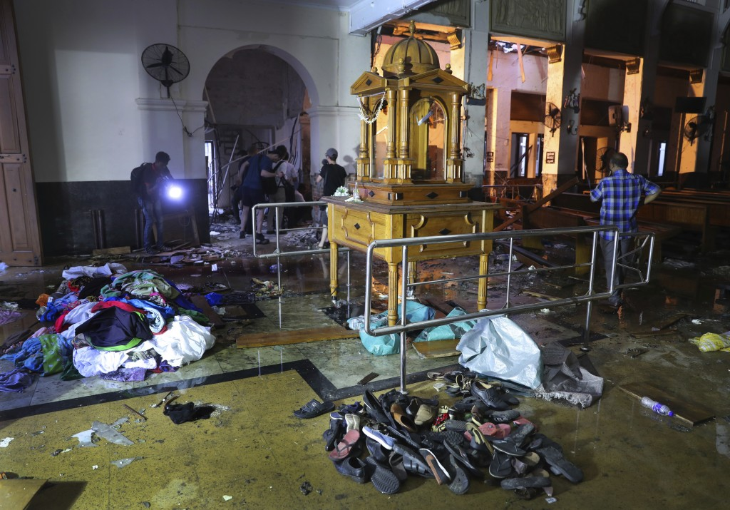 Shoes and other belongings left by panicked worshippers are seen stacked up inside St. Anthony's Church in Colombo, Sri Lanka, Friday, April 26, 2019....