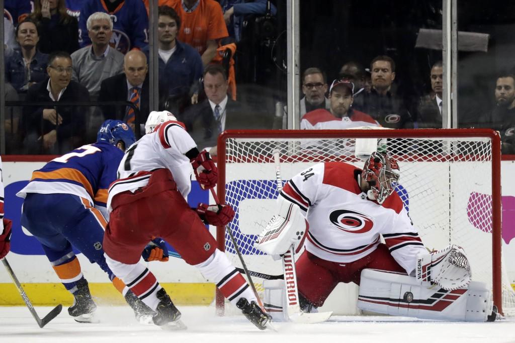 Carolina Hurricanes goaltender Petr Mrazek, right, of the Czech Republic, blocks a shot form New York Islanders left wing Anders Lee, left, during the...