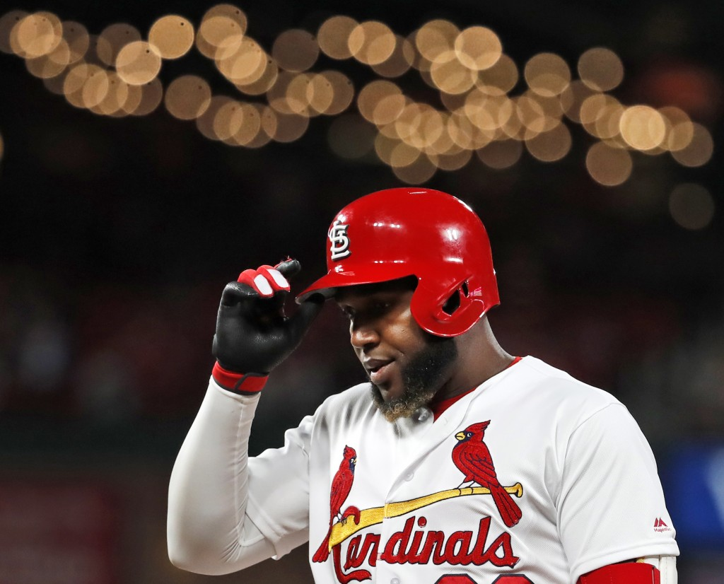 St. Louis Cardinals' Marcell Ozuna removes his helmet after popping out to end the seventh inning of a baseball game against the Cincinnati Reds Frida...