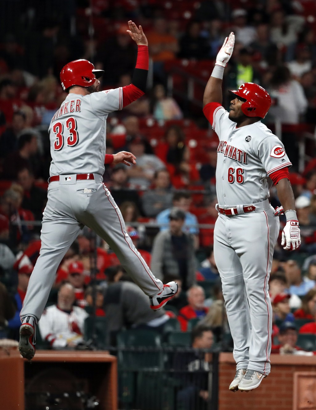 Cincinnati Reds' Yasiel Puig (66) is congratulated by teammate Jesse Winker (33) after hitting a two-run home run during the eighth inning of a baseba...