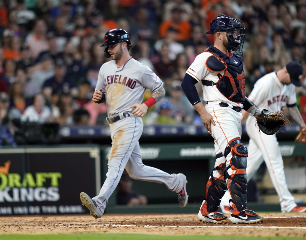 Cleveland Indians' Tyler Naquin, left, scores as Houston Astros catcher Max Stassi stands in front of home plate during the seventh inning of a baseba...