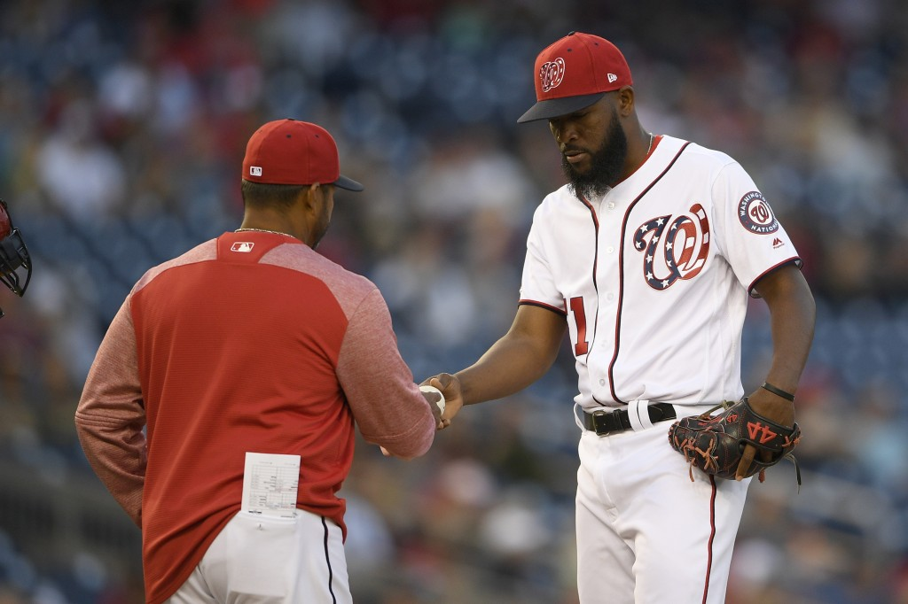Washington Nationals relief pitcher Wander Suero, right, is pulled by manager Dave Martinez, left, during the 10th inning of a baseball game against t...