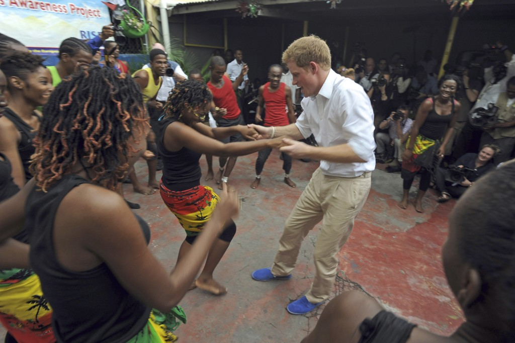 FILE - In this Tuesday, March 6, 2012 file photo, Britain's Prince Harry dances with a girl during a visit to the non-governmental organization RISE (...