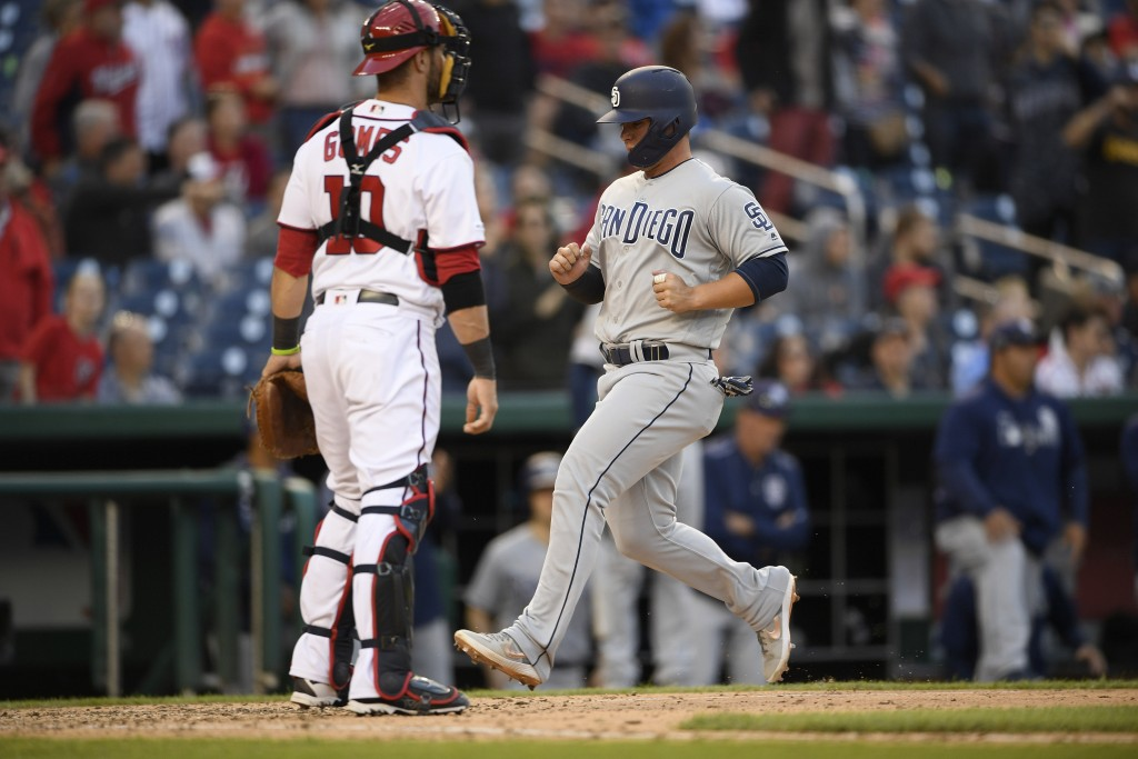 San Diego Padres' Ty France, right, comes home to score on a sacrifice fly by Greg Garcia during the 10th inning of a baseball game as Washington Nati...