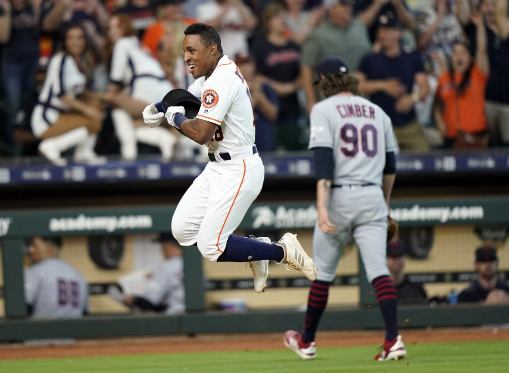 Houston Astros' Tony Kemp, left, celebrates after hitting the game-winning home run as Cleveland Indians relief pitcher Adam Cimber (90) walks to the ...