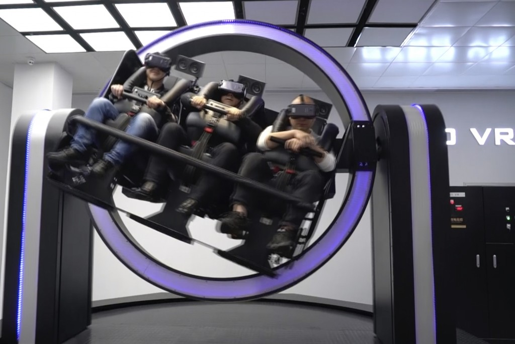 """In this April 2, 2019, photo, Liu Zixing, a mining ore businessman, right, rides a virtual reality """"gyroscope"""" in a VR theme park in Nanchang, China. ..."""