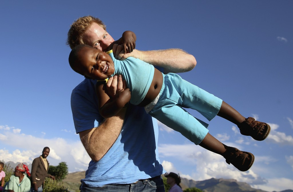 FILE - In this file photo taken on Dec. 6 2014, Britain's Prince Harry swings young three year old orphan boy  Lerato in this photograph taken with th...