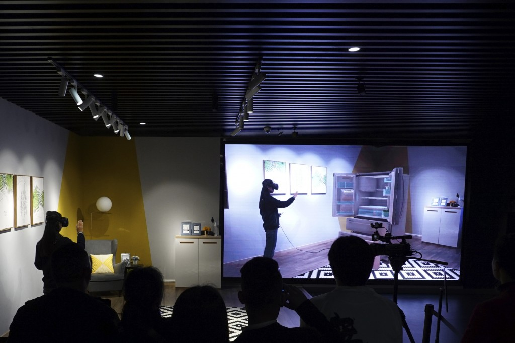 In this April 2, 2019, photo, visitors watch a virtual reality shopping demonstration in a VR exhibit hall in Nanchang, China. The exhibit hall is par...