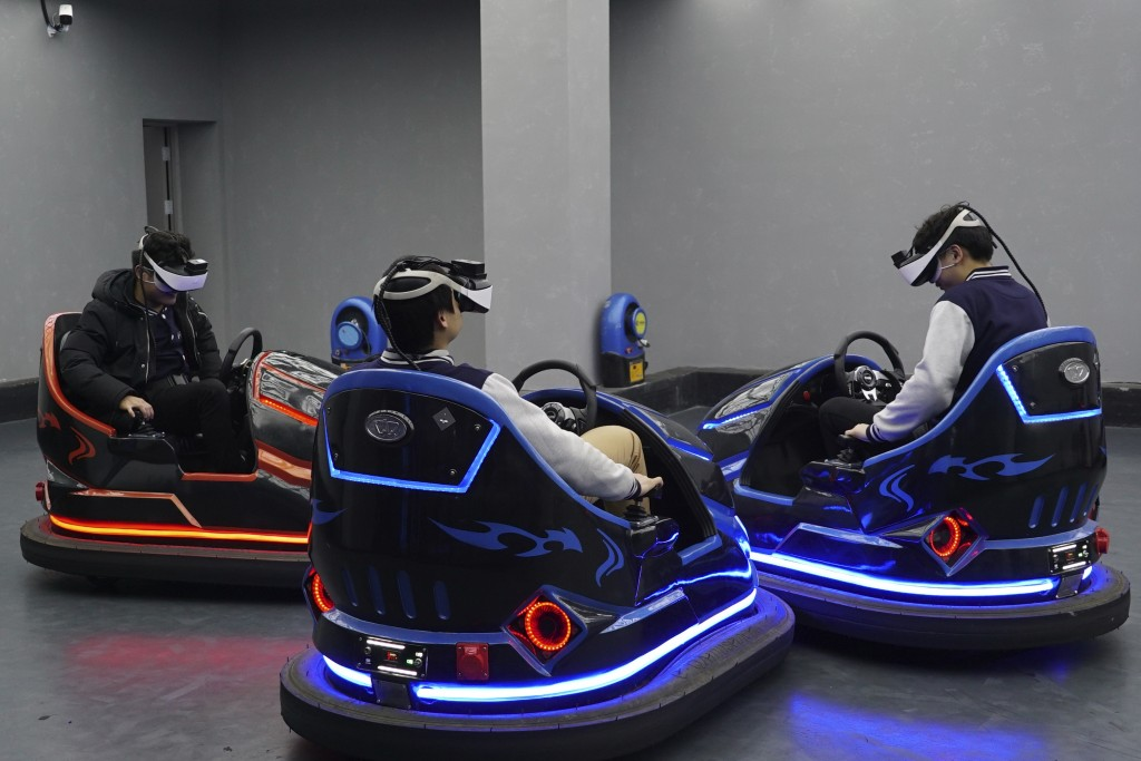 In this April 2, 2019, photo, visitors drive virtual reality bumper cars in a VR theme park in Nanchang, China. One of the largest virtual reality the