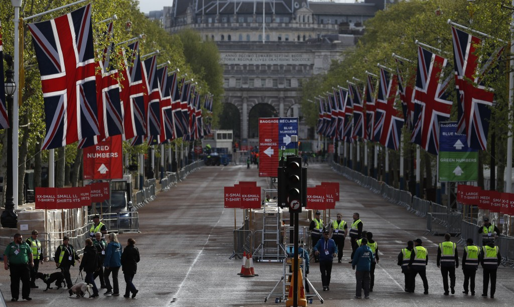 Security and police walk down the Mall as preparations are made for the finish line area of the 39th London Marathon in London, Sunday, April 28, 2019...