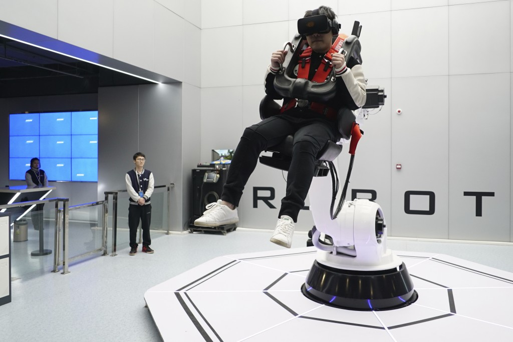 In this April 2, 2019, photo, a visitor rides a virtual roller coaster ride operated by a robotic arm in a VR theme park in Nanchang, China. One of th