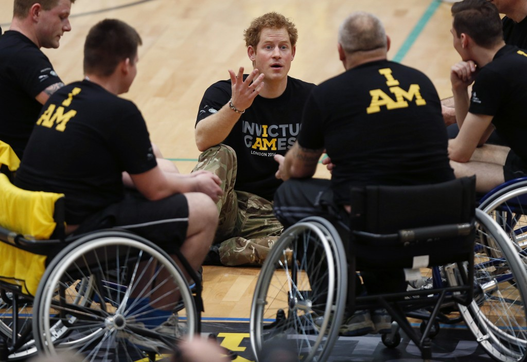 FILE - In this Thursday, March 6, 2014 file photo, Britain Prince Harry, center, speaks to the wheelchair basketball competitors during the launch of ...