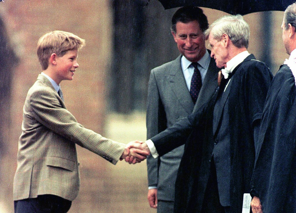 FILE - In this Wednesday, Sept. 2, 1998 file photo, Britain's Prince Harry meets Headmaster John Lewis, right, as Prince Charles looks on, after his a...