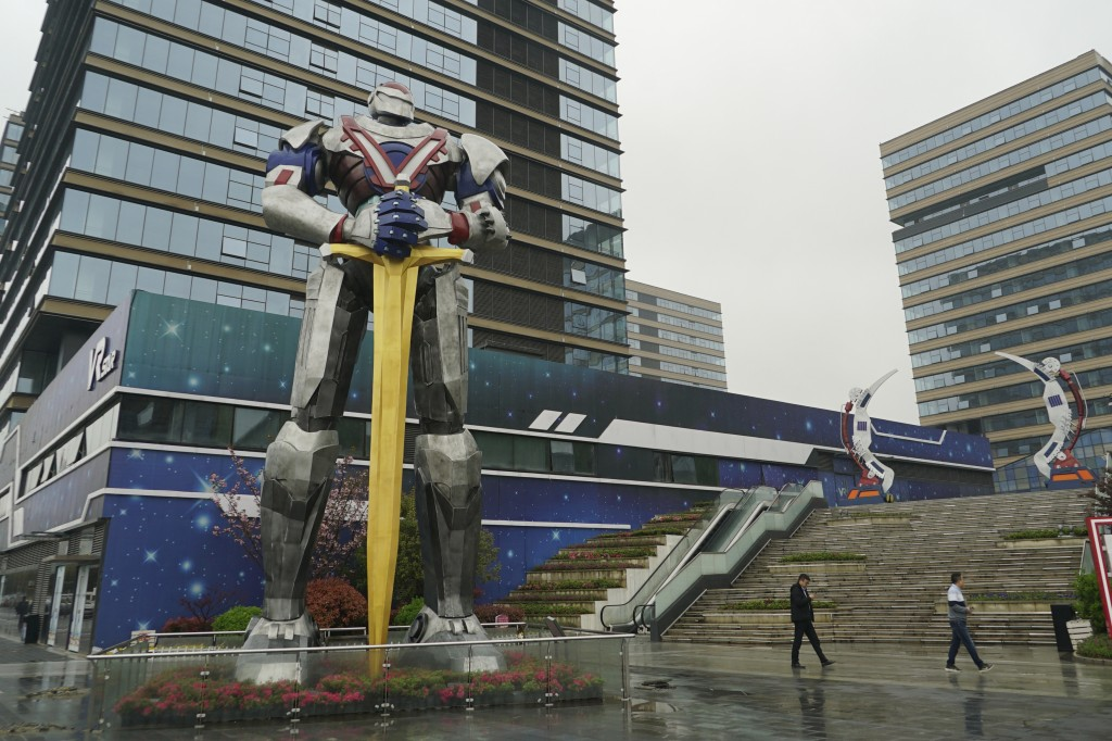 """In this April 2, 2019, photo, people walk by a giant robot statue at a virtual reality """"base"""" in Nanchang, China. The city is trying to position itsel"""