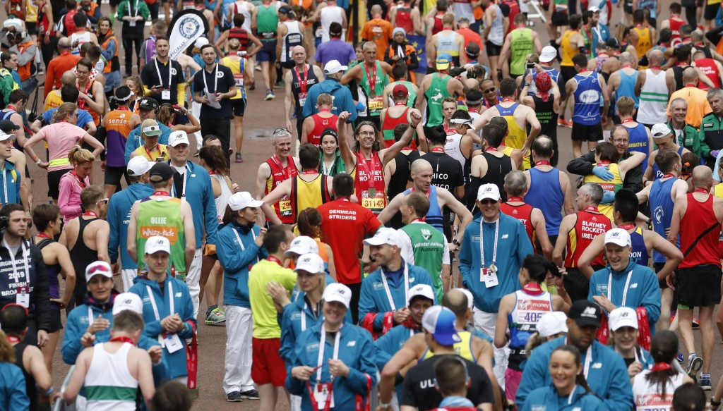A competitor in the 39th London Marathon, centre, turns round and raises his arms in triumph after he competed the marathon and shares an moment with ...