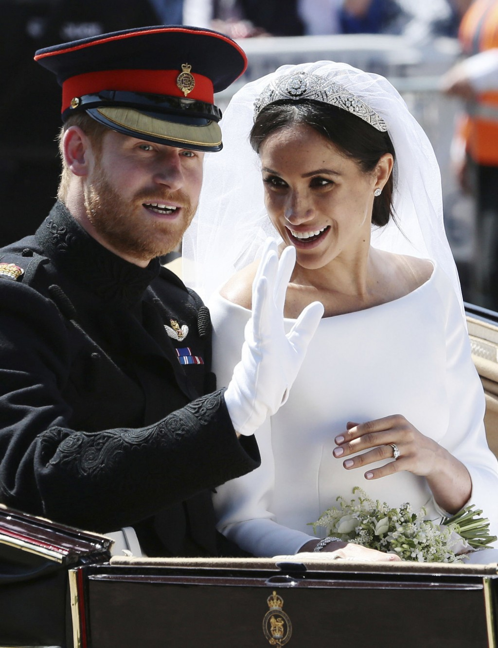 FILE - In this Saturday, May 19, 2018 file photo, Britain's Prince Harry and Meghan Markle ride in an open-topped carriage after their wedding ceremon...