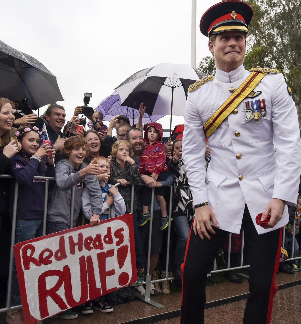 """FILE - In this Monday, April 6, 2015 file photo, Britain's Prince Harry, right, reacts after shaking hands with kids holding up a sign reading """"Red He..."""